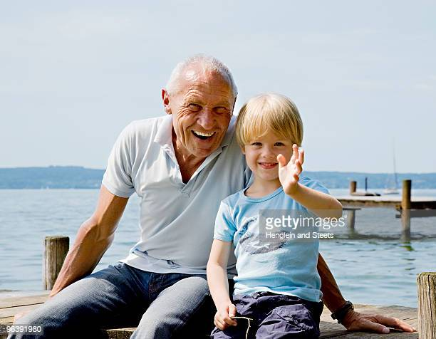 boy with grandfather on pier at lake
