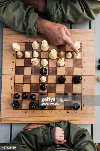Boy with grandfather playing chess, high angle view