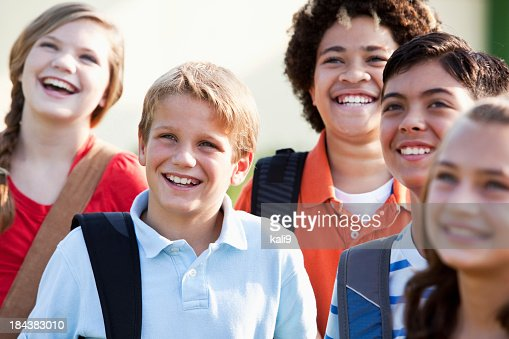Menino com grupo de amigos carregar bookbags