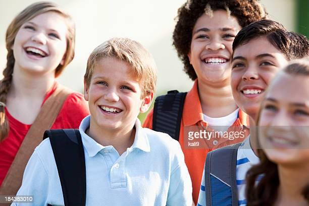 Ragazzo con un gruppo di amici che trasportano cartella,