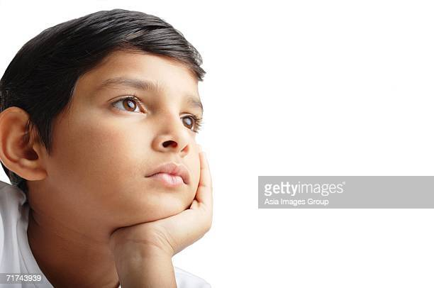 Boy with hand on chin, looking away