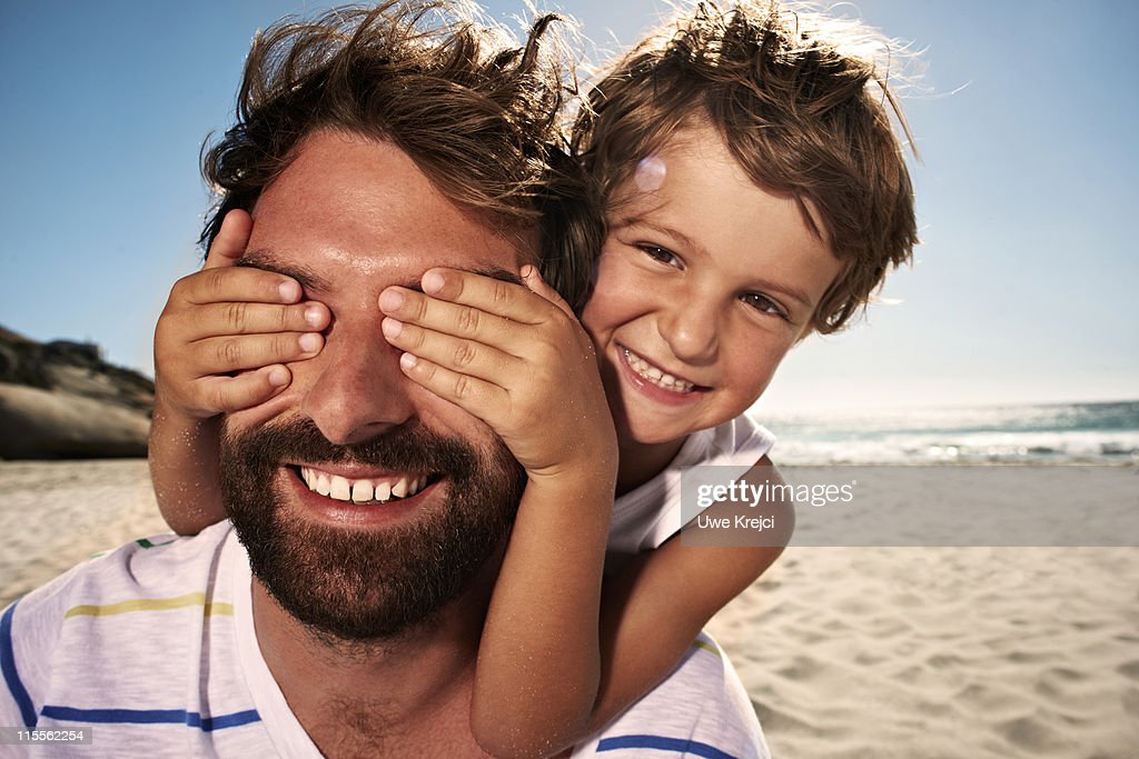 Boy (4-5) with hand over fathers eyes, close up