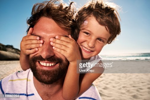 Boy (4-5) with hand over fathers eyes, close up : Stock Photo