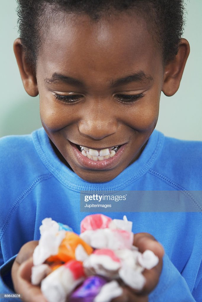 Boy with handful of candy : Stock Photo
