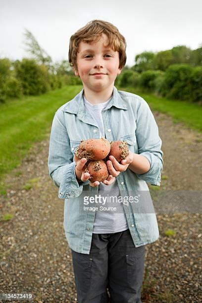 Boy with handful of potatoes