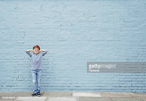 Boy with hands covering his ears