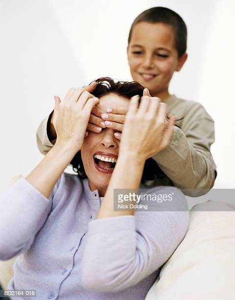 Boy (9-11) with hands over mother's eyes, smiling, close-up