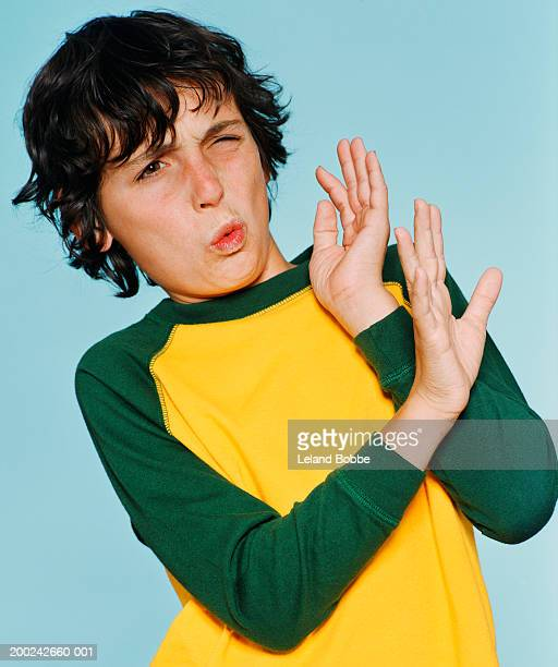 Boy (10-12) with hands up, making a face