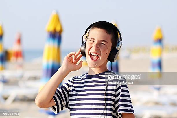 Boy with headphones listening to music at beach