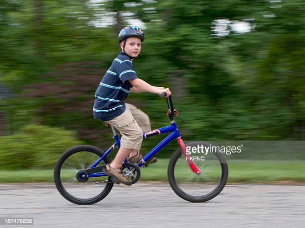 Boy With Helmet Riding Fast On Bike, Looking At Camera