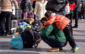 A boy with his father and grandma waits on the square of Beijing west railway station China's 40day spring travel rush called 'chunyunthe largest...