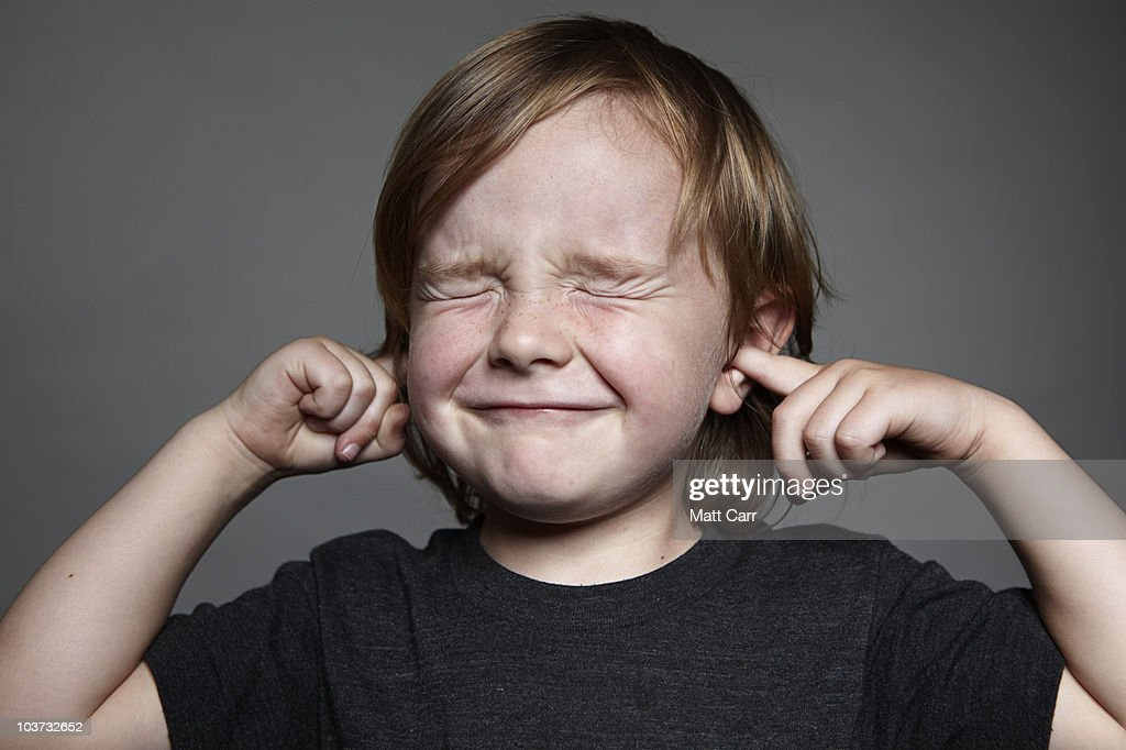 Boy with his fingers in his ears.