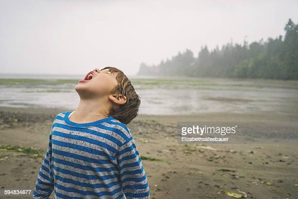 Boy with his head tilted back catching rain in mouth