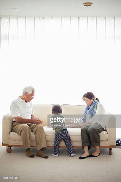 Boy with his mother and grandfather on sofa