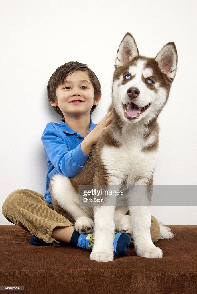 Boy with his puppy sitting on his lap