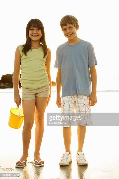 Boy with his sister holding bucket on beach