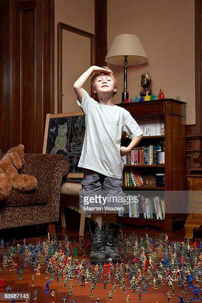 Boy with his toy soldiers, giving a salute