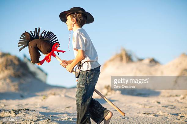 Boy with hobby horse dressed as cowboy in sand dunes