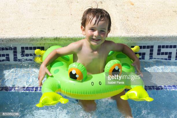 Boy with inflatable ring at swimming pool