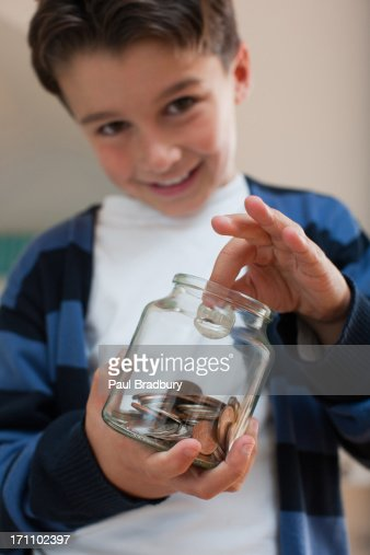 Boy with jar of coins : Stock Photo