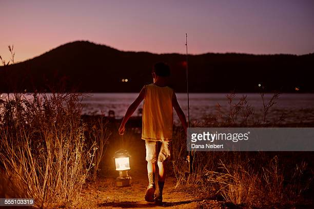 Boy with lantern and fishing rod & tackle on lake