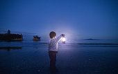 Boy holding lantern in his hand and looking towards beach. could be waiting for someone or a metaphor of hope or spirituality.