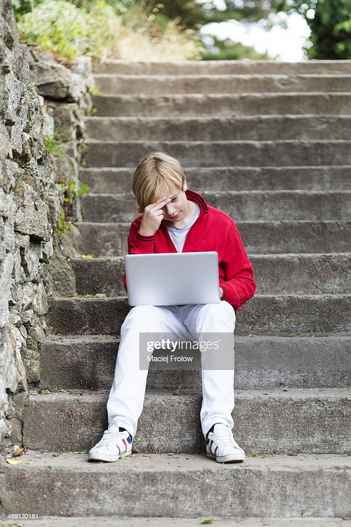 Boy with laptop outdoors : Stock Photo