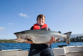 Boy (11-13) with large salmon that he caught, portrait