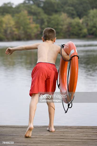 Boy with life preserver leaning over edge of pier