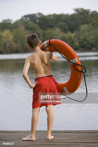 Boy with life preserver on pier looking at lake