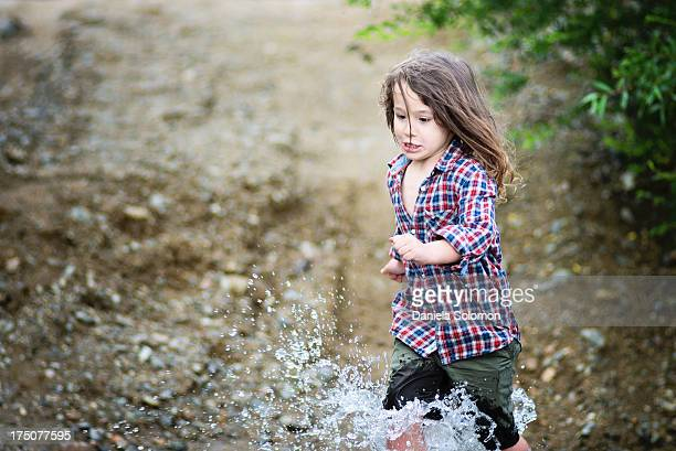 Boy with long hair running in the water