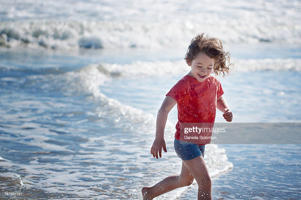 Boy with long hair running on the beach : Stock Photo