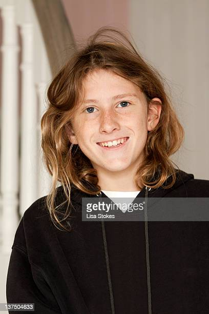 Boy with long hair standing on stairs