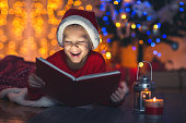 Surprised child opening magic Christmas book. Xmas holiday concept