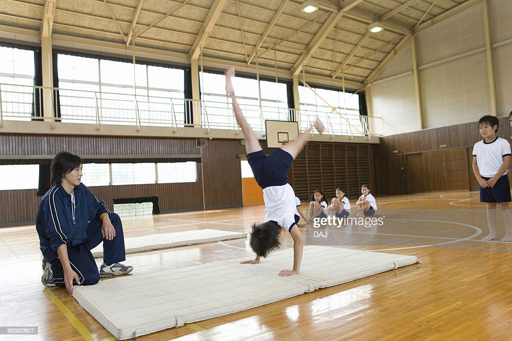 Boy with male teacher exercising on mat, blurred motion