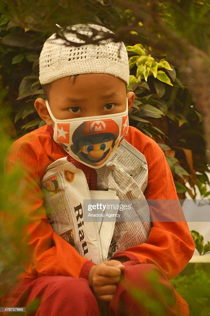 A boy with mask prays for rainfall to make haze disappeared on March 14, 2014 in Pekanbaru, Riau, Indonesia. Smoke haze from forest fires that still covered the Riau province causing many schools were closed and sick people breathing.