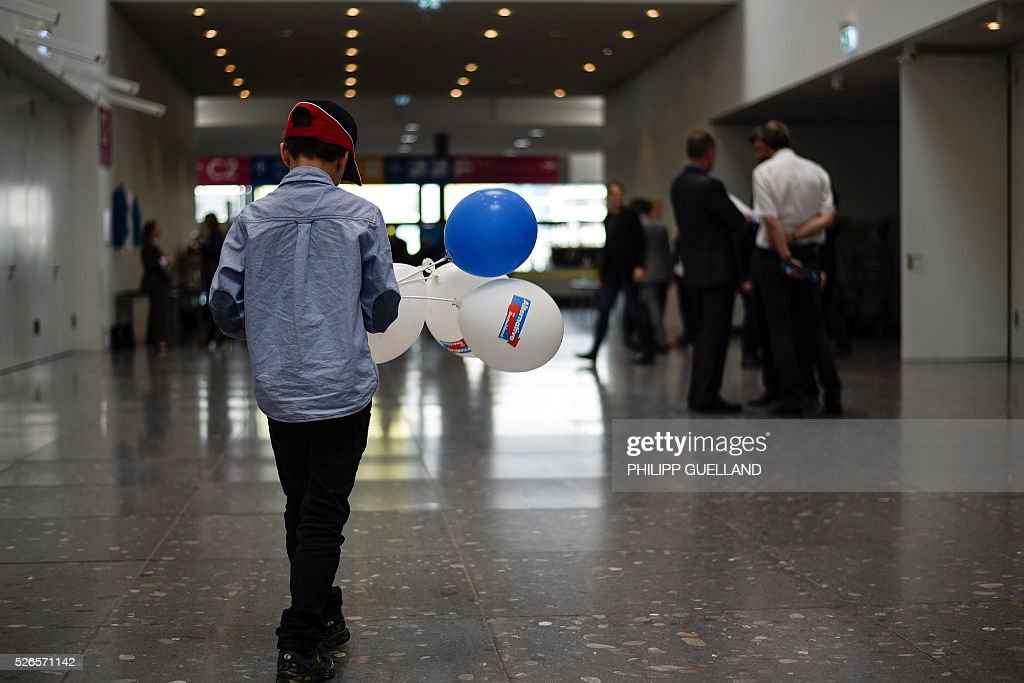 A boy with merchandise balloons at the venue of the german right wing party Alternative for Germany (AfD) at the the Stuttgart Congress Centre ICS on April 30, 2016. The Alternative for Germany (AfD) party is meeting in the western city of Stuttgart, where it is expected to adopt an anti-Islamic manifesto, emboldened by the rise of European anti-migrant groups like Austria's Freedom Party. / AFP / Philipp GUELLAND