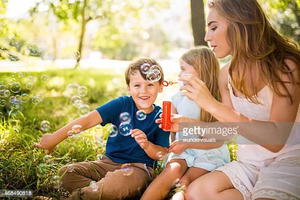Garçon avec maman et sœur s'amuser avec des bulles
