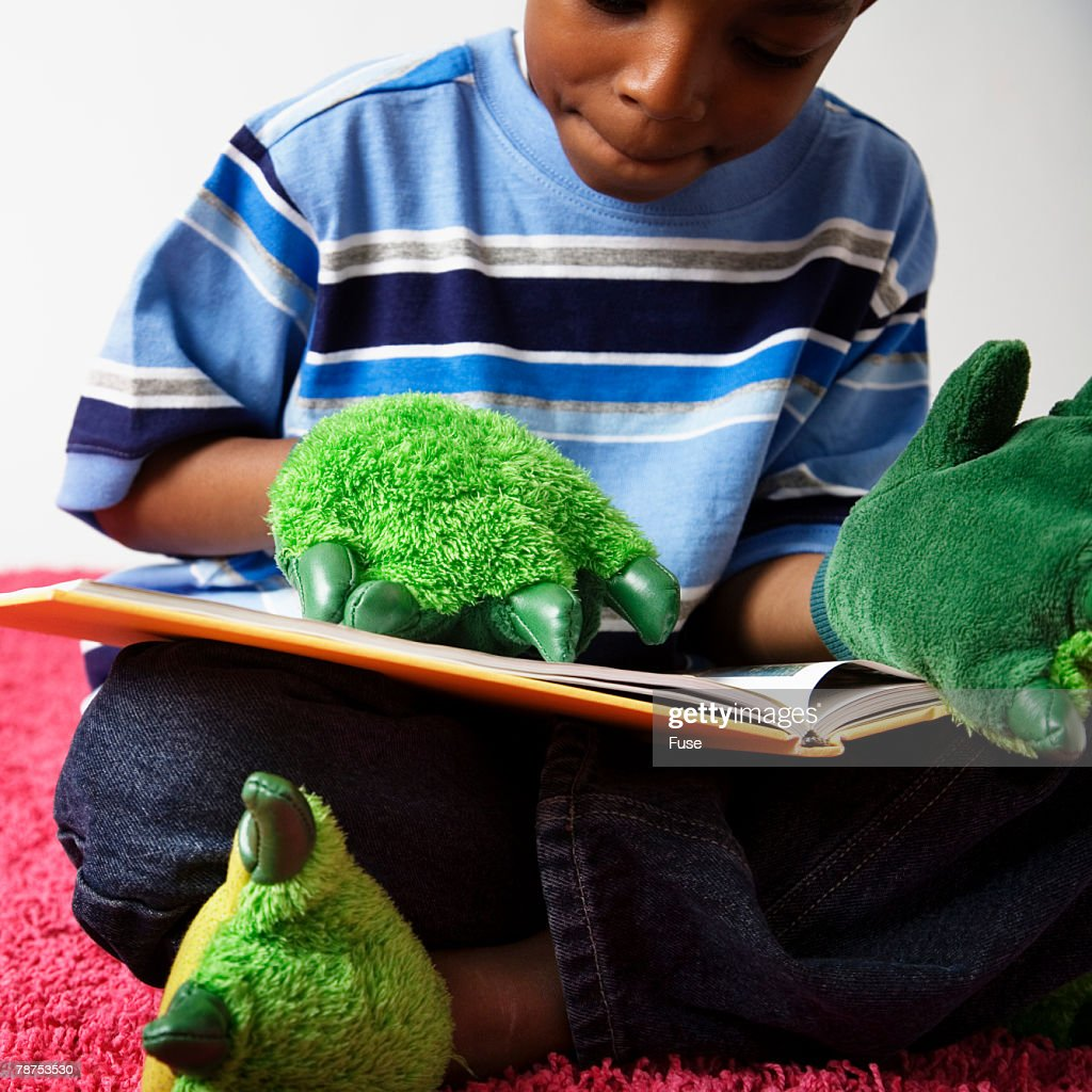 Boy with Monster Gloves and Slippers Reading Book