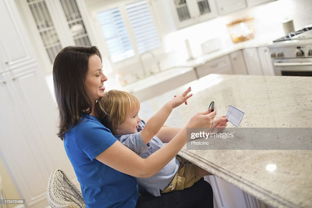 Boy With Mother Depositing Check Through Mobile Phone