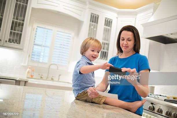 Boy With Mother Depositing Check Through Smart Phone