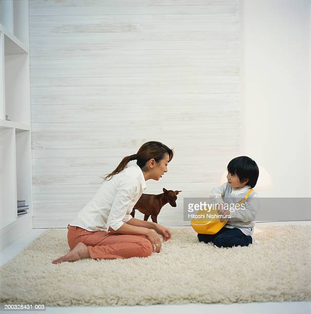 Boy (2-5) with mother sitting on rug