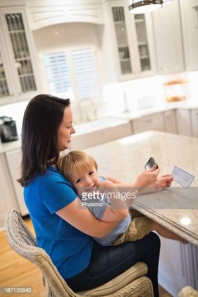 Boy With Mother Using Smart Phone To Deposit Check