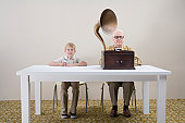 Boy (10-11) with mp3 player and man with gramophone sitting at table