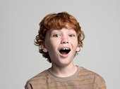 Boy (8-9 years) with open mouth, portrait, studio shot