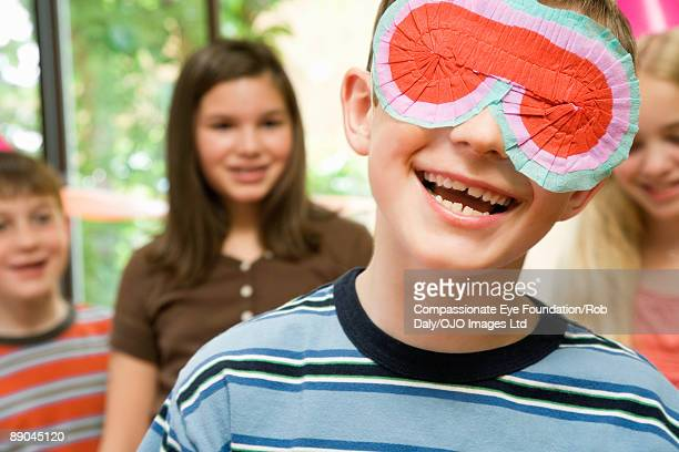 boy with other kids wearing a festive blindfold