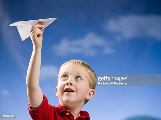 Boy with paper airplane outdoors