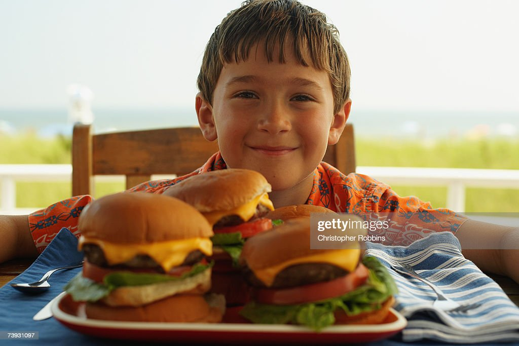 Boy (8-9) with plate of four hamburgers : Stock Photo