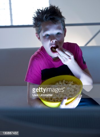 Boy with popcorn watching television : Stock Photo