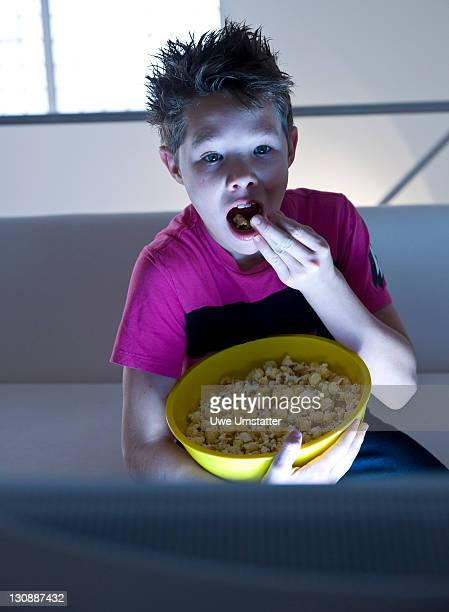 Boy with popcorn watching television